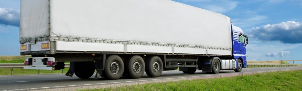 Zijaanzicht van blauw/witte vrachtwagen die over de Nederlandse weg rijdt