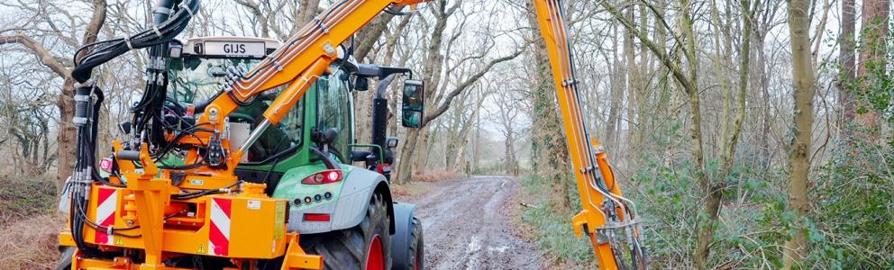 Achteraanzicht van tractor van Staatsbosbeheer in het bos